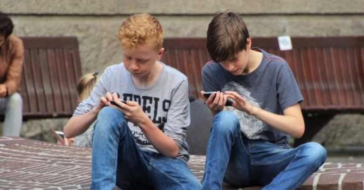 Teenage boys play with their mobile phones.
