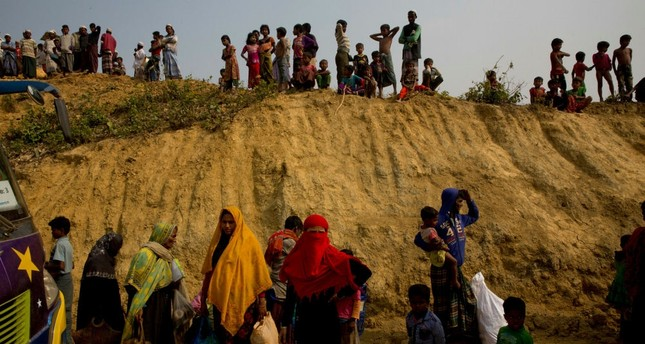 Rohingya Muslims watch from atop a hill as new refugees arrive in Balukhali refugee camp, Bangladesh, Jan. 14.