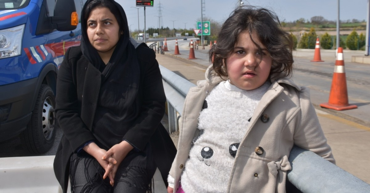 A migrant woman and a girl wait next to a gendarme vehicle after a group of migrants were stopped on the road to Edirne, April 4, 2019.