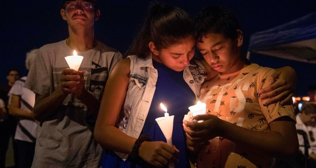 People hold candles as they pray during a candlelight vigil at the Immanuel Church for victims of a shooting that left a total of 22 people dead at the Cielo Vista Mall WalMart in El Paso, Texas, on Aug. 5, 2019. AFP Photo