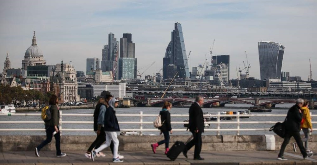 In this file photo, pedestrians walk with the London skyline in the background, Oct. 27, 2016. (AFP Photo)