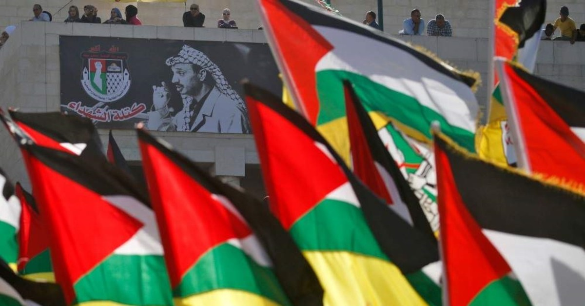 Demonstrators wave Palestinian flags next to a portrait of late leader Yasser Arafat on the 15th anniversary of his death, during a gathering in Nablus in the occupied West Bank, Nov. 12, 2019. (AFP Photo)