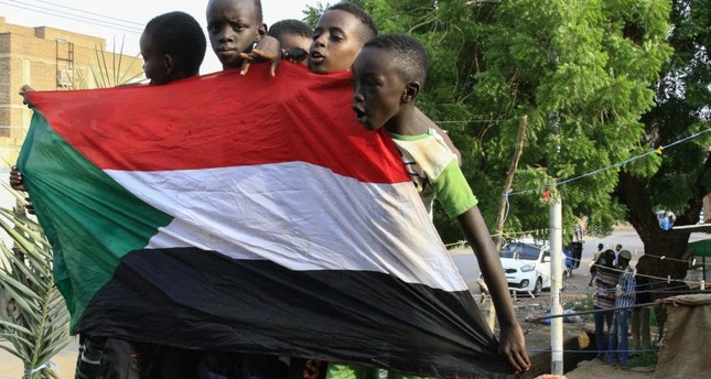 Young Sudanese boys carry a national flag as they celebrate the historic transitional constitution, Bahri, Aug. 18, 2019.
