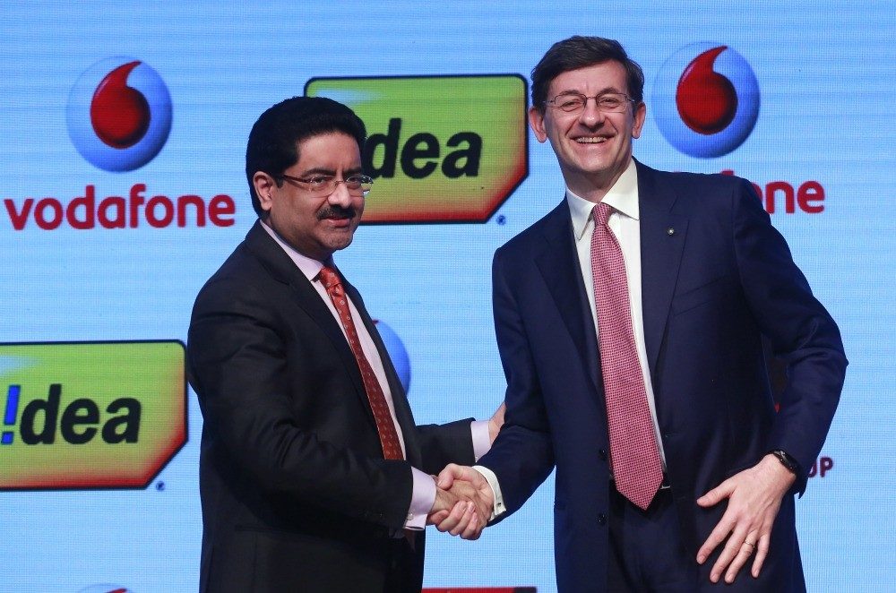 Kumar Mangalam Birla (L), chairman of Aditya Birla Group, shakes hands with Vittorio Colao, CEO of Vodafone Group, after a news conference in Mumbai, yesterday.