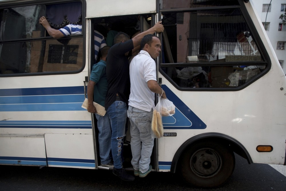 A man hangs off of a bus clutching a bag of bread, outside a bakery in Caracas.