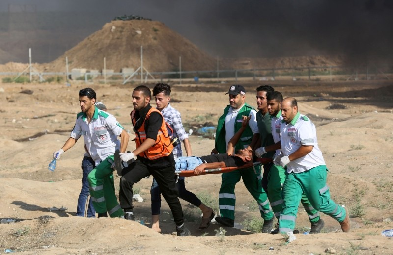 Palestinian paramedics carry a wounded protester away from the scene of clashes with Israeli forces during a weekly demonstration against the expropriation of Palestinian land by Israel, east of Gaza City on July 6, 2018. (AFP Photo)