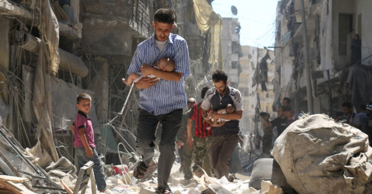 Syrian men carrying babies make their way through the rubble of destroyed buildings following a reported air strike on the opposition-held Salihin neighbourhood of the northern city of Aleppo, on September 11, 2016 (AFP Photo)