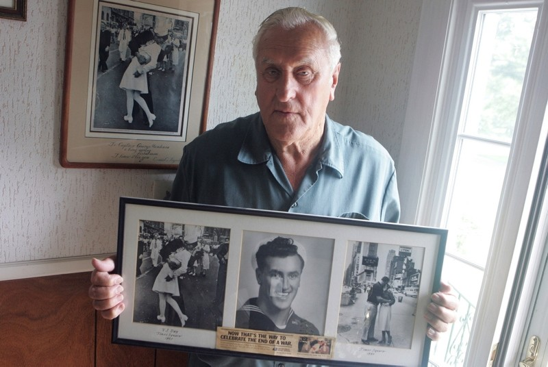 In this July 2, 2009, photo George Mendonsa poses for a photo in Middletown, R.I., holding a copy of the famous Alfred Eisenstadt photo of Mendonsa kissing a woman in a nurse's uniform in Times Square on Aug. 14, 1945 (Providence Journal via AP)