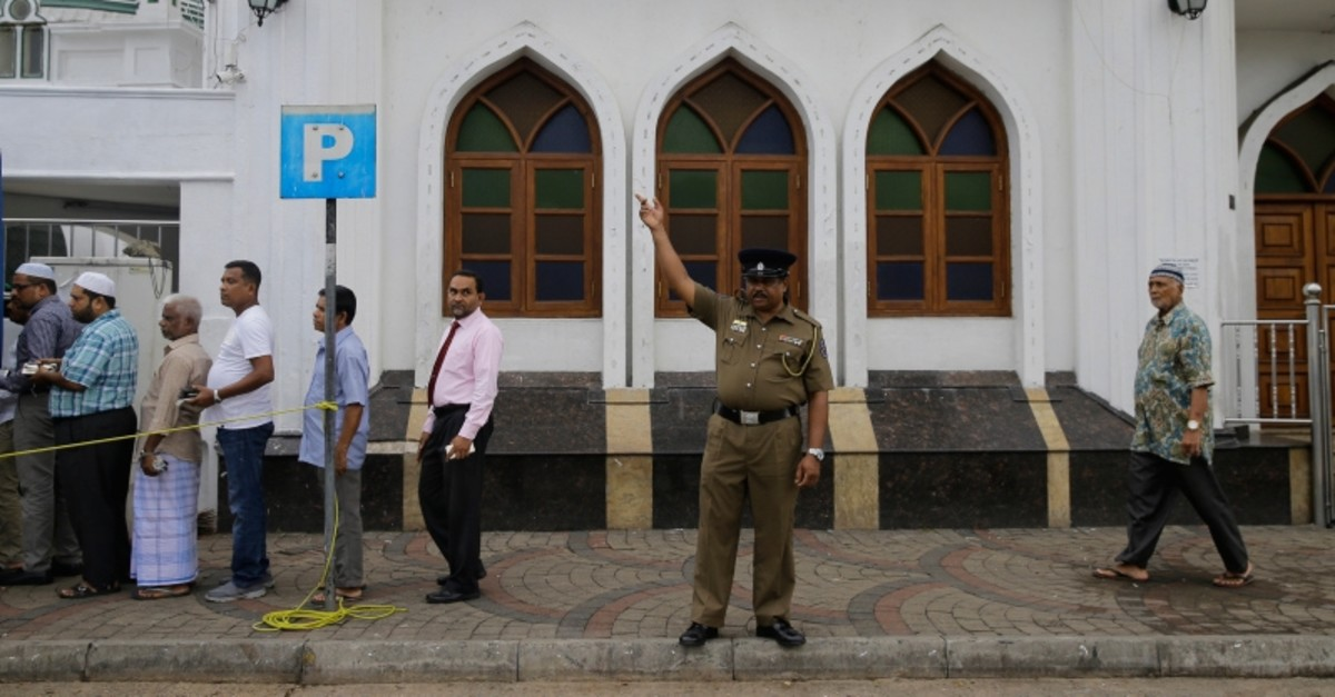 Sri Lankan Muslims arrive to attend Friday prayers at a mosque as a police officer stands guard in Colombo, Sri Lanka, Friday, May 3, 2019. (AP Photo)