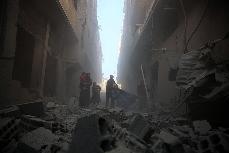 A family walks through a street covered with rubble from a heavily damaged building following airstrikes by the Assad regime forces on Arbin, in the opposition-held Eastern Ghouta region on the outskirts of Damascus, Syria, Feb. 1, 2018. (AFP Photo)