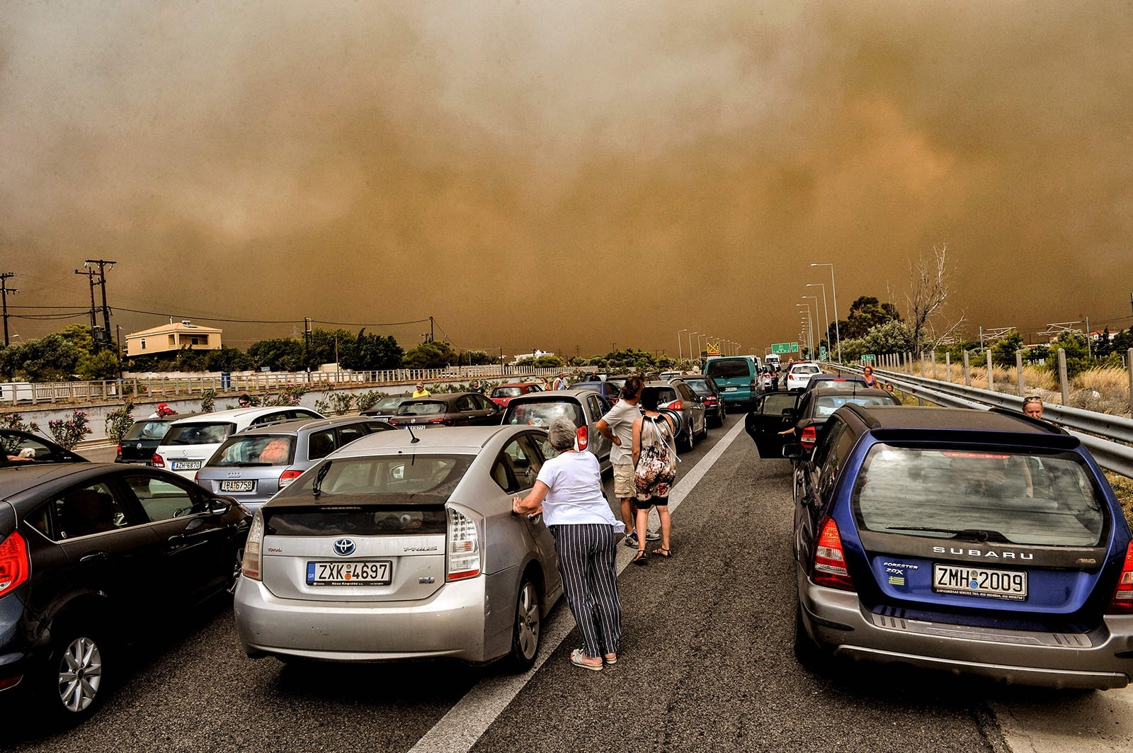 Cars are blocked at the closed National Road during a wildfire in Kineta, near Athens, on July 23, 2018.