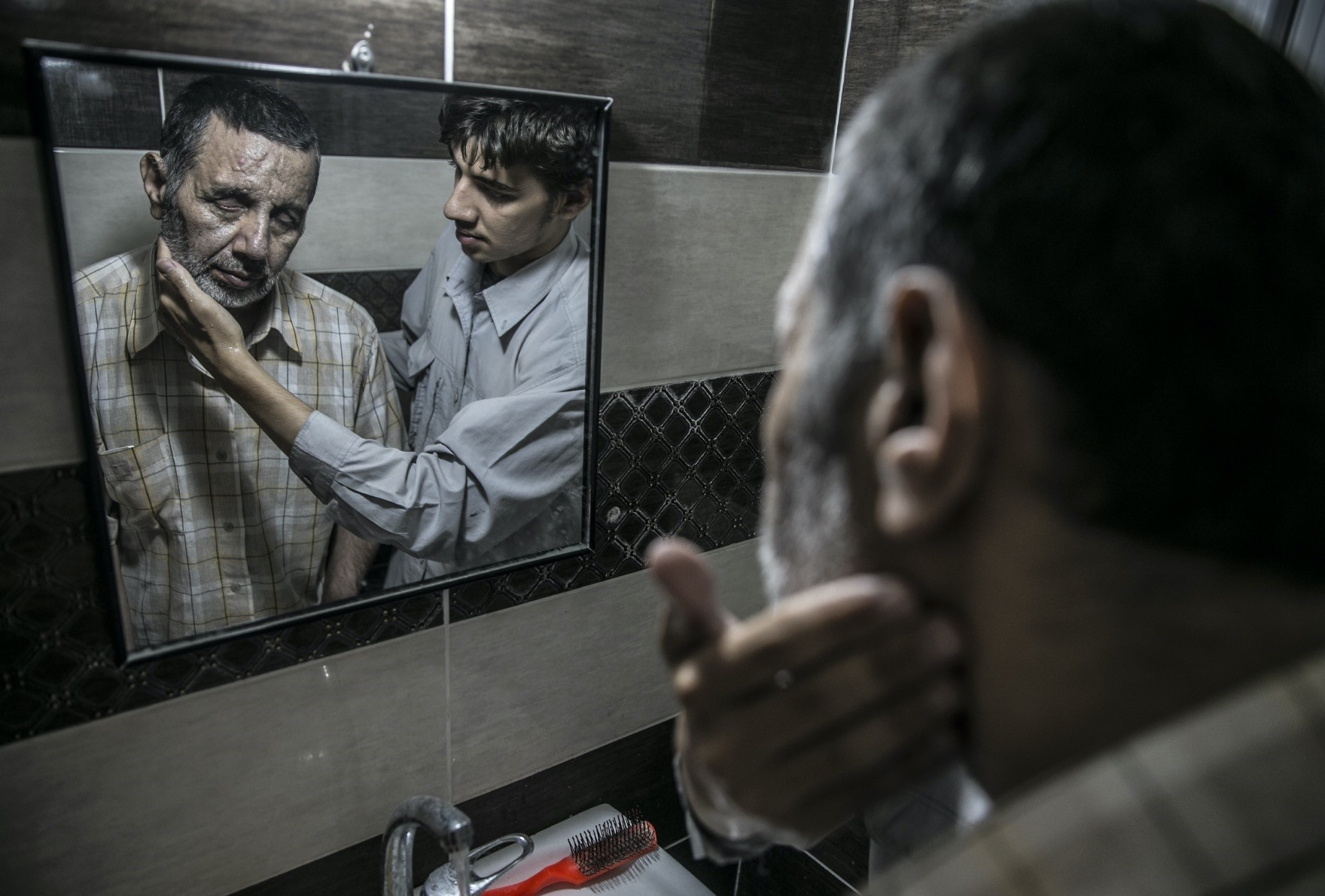 Muhammed Bessam Al Meydani who lost his eyesight during an attack orchestrated by the Assad regime. He continues to his daily routine with the help of his son Kenen Al Meydani.