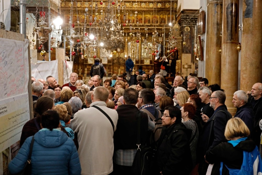 A group of tourists and pilgrims visit the Church of the Nativity, the place where Jesus is said to have been born, in the occupied biblical West Bank town of Bethlehem.