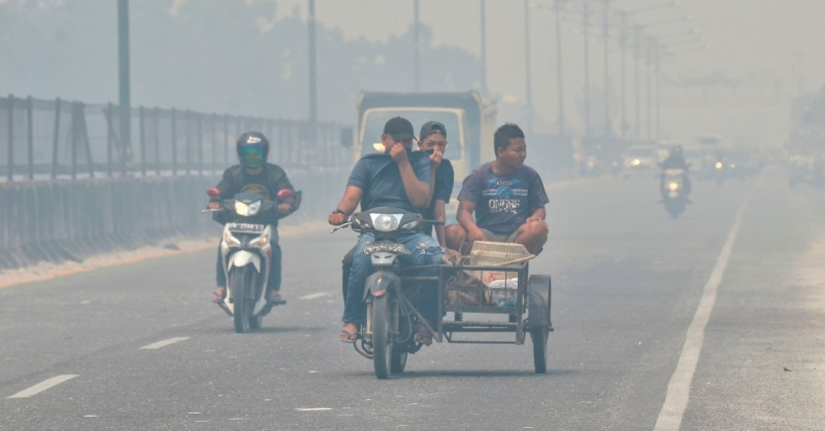 Motorists make their way along a street in Kampar, Riau on Sept. 17, 2019 which is covered in thick haze. (AFP Photo)
