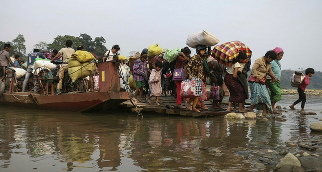 Displaced Kachin residents cross the Malikha river on a ferry to escape Myanmar army atrocities, April 26.