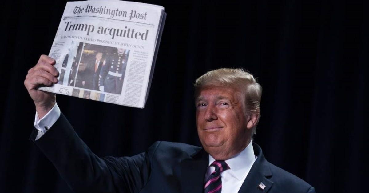 President Donald Trump holds up a newspaper during the 68th annual National Prayer Breakfast, at the Washington Hilton, Thursday, Feb. 6, 2020, in Washington. (AP Photo/ Evan Vucci)