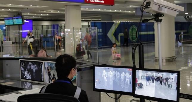 A health surveillance officer monitors passengers arriving at the Hong Kong International airport, Hong Kong, Jan. 4, 2020. AP Photo