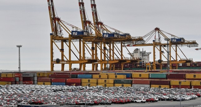 Cars for export and import are stored in front of containers on Thursday, May 16, 2019 at the harbor in Bremerhaven, Germany. AP Photo