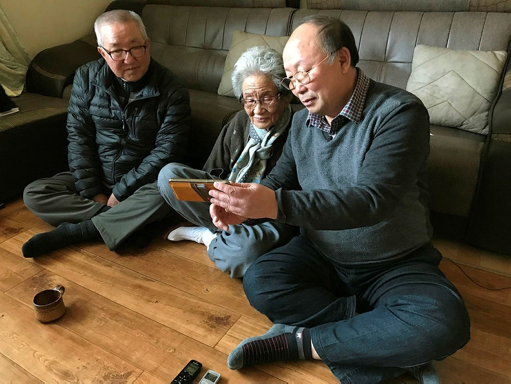 Kang Hwa-seon, center, sits with her nephew Song Yong-geun, left, and her son Song Young-jin at her home in Gangneung, South Korea, looking at pictures of a 2015 family reunion she had with her brother-in-law.  (AP Photo)