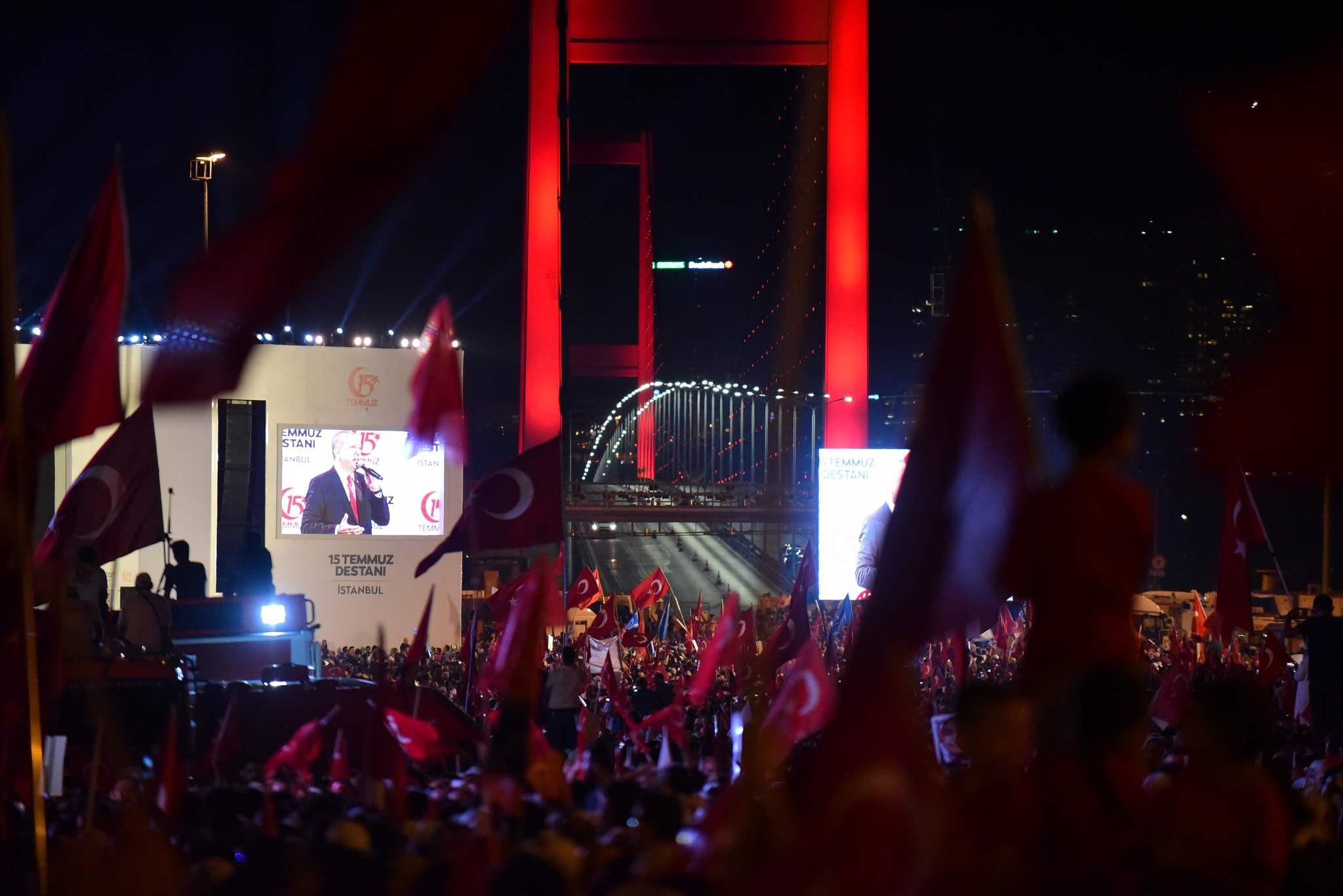 People wave Turkish national flags during the first anniversary of the failed coup on the July 15 Martyrs Bridge, Istanbul, July 15.