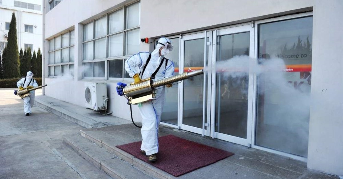Workers in protective suits spray disinfectant at a business in Qingdao in eastern China's Shandong Province, Feb. 1, 2020. (Chinatopix via AP)