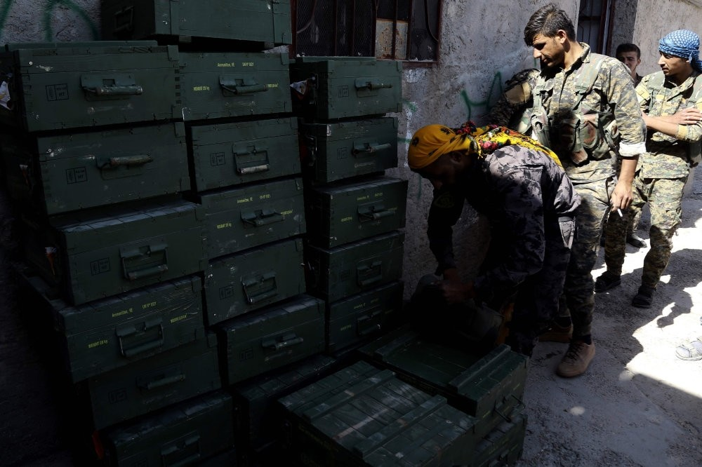 Syrian Democratic Forces (SDF), made up of an alliance of PKK-affiliated YPG fighters, unload boxes of ammunition supplied by the U.S. in a village north of Raqqa, June 7.