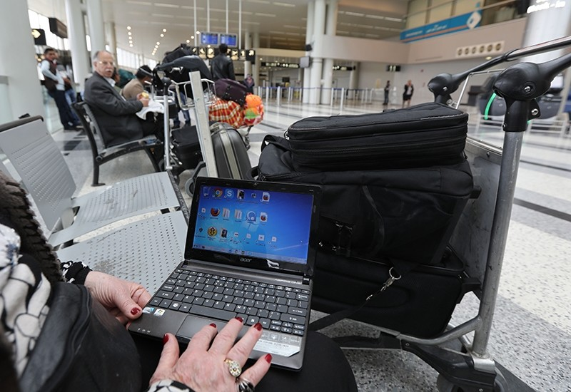 This file photo taken on March 22, 2017 shows a Syrian woman travelling to the United States through Amman opens her laptop before checking in at Beirut international airport. (AFP Photo)