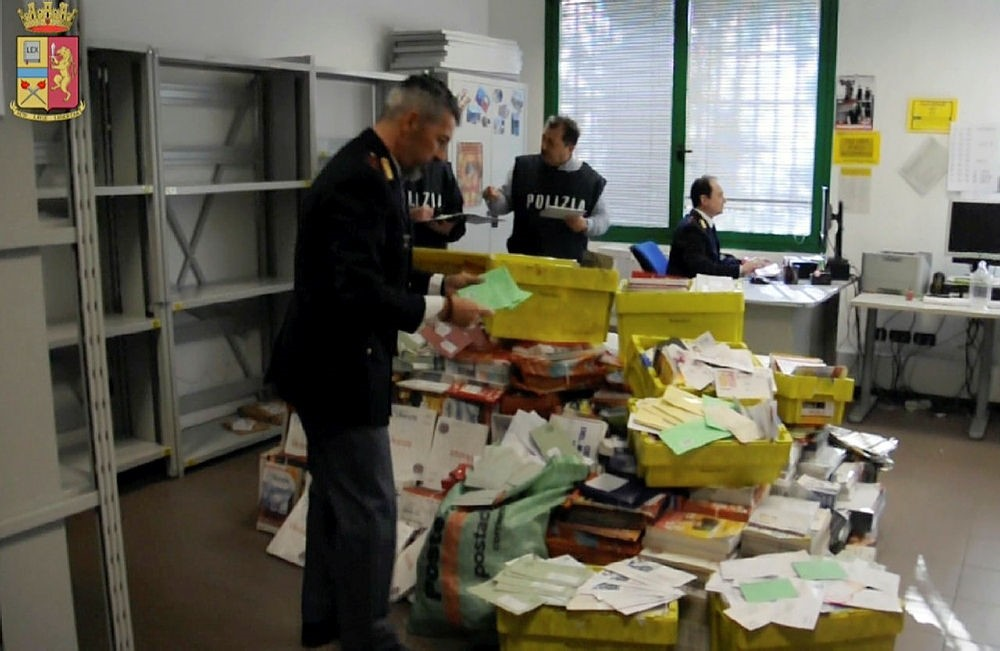 This frame made from a video by the Italian police made available Jan. 31, 2018 shows postal police officers sorting out undelivered mail found in a postman's garage, in Vicenza, northern Italy. (AP Photo)