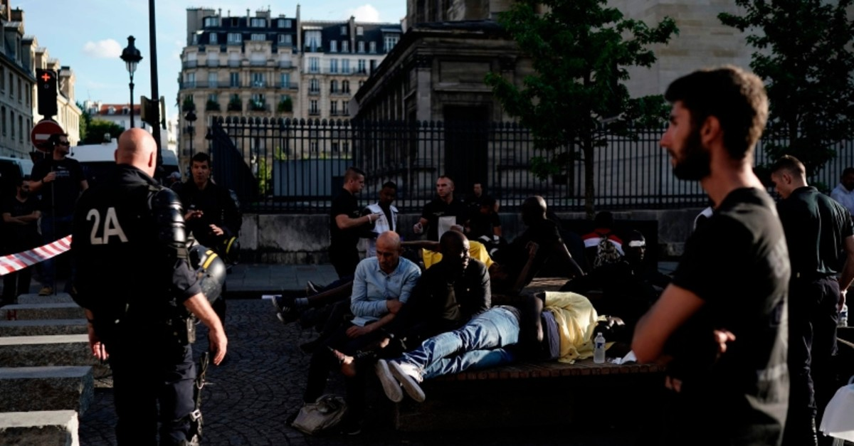 Protesters, injured during the evacuation by police, wait prior to receiving medical assistance by firefighters, on July 12, 2019, in Paris. (AFP Photo)