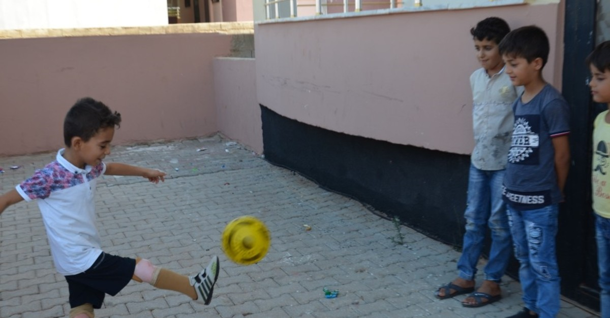 Muhammed Lamot, an 8-year-old orphan who was given prostheses, plays football with his friends, Sept. 3, 2019.