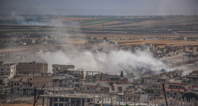 Plumes of smoke rise following reported Syrian regime forces' bombardment of the town of Khan Sheikhun in the southern countryside of Idlib province, June 5, 2019.