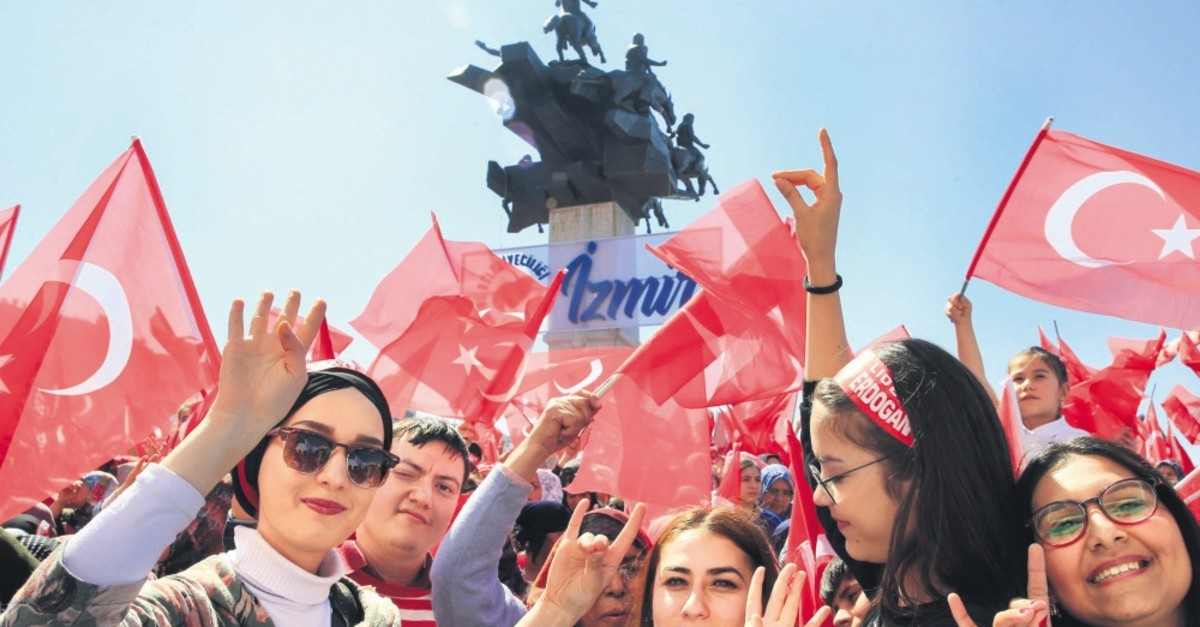 People attending the joint rally held by the People's Alliance make the symbolic hand signs for both the AK Party and MHP in u0130zmir, March 17, 2019.