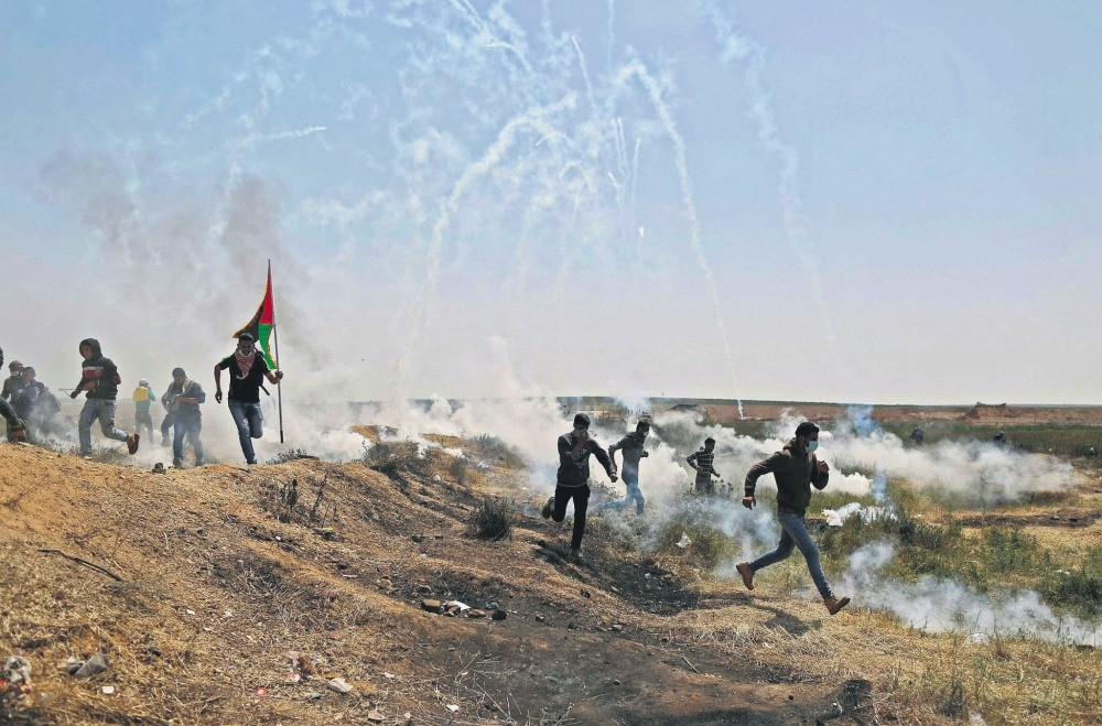 Palestinians run for cover from tears gas at the Israel-Gaza border, Gaza Strip, April 6.