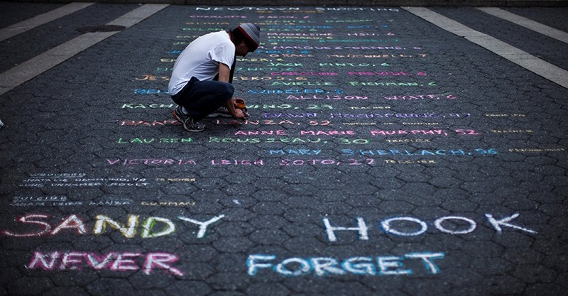 Street artist Mark Panzarino, 41, prepares a memorial as he writes the names of the Sandy Hook Elementary School victims during the six-month anniversary of the massacre (Reuters File Photo)