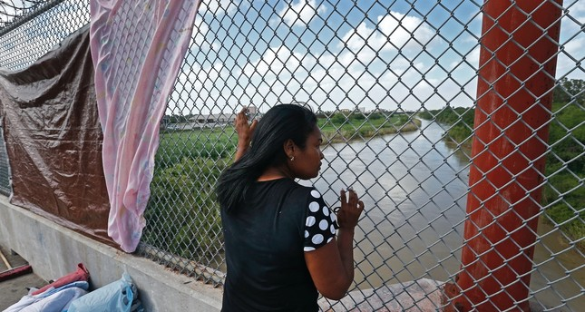 An immigrant from Cuba seeking asylum looks out across the Rio Grande River while waiting on the middle of a bridge to get into the United States from Matamoros, Mexico.