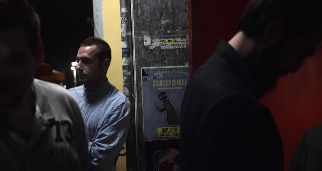 People wait outside a bar to listen to stand-up in Thessaloniki.