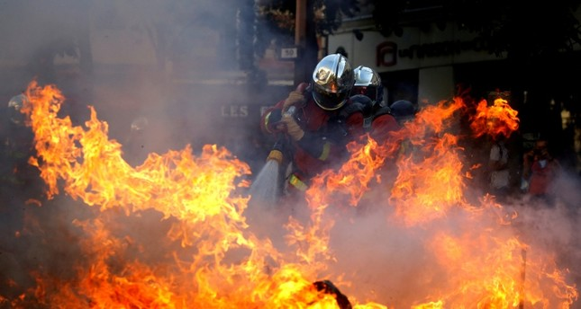 Firefighters extinguish a barricade during a protest urging authorities to take emergency measures against climate change, in Paris, France, September 21, 2019 (Reuters Photo)