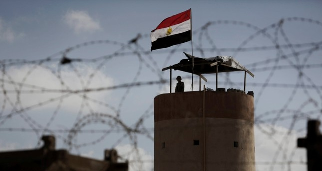 A file photo dated July 1, 2013 shows an Egyptian security guard on duty in a watch tower at the border post between Egypt and Gaza Strip in Rafah town. (EPA Photo)