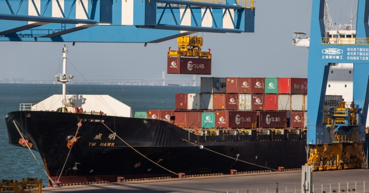A crane loads a container on a ship at a fully automatic container berth of Port of Qingdao in Qingdao city, eastern China's Shandong province, Oct. 18, 2018. (EPA Photo)