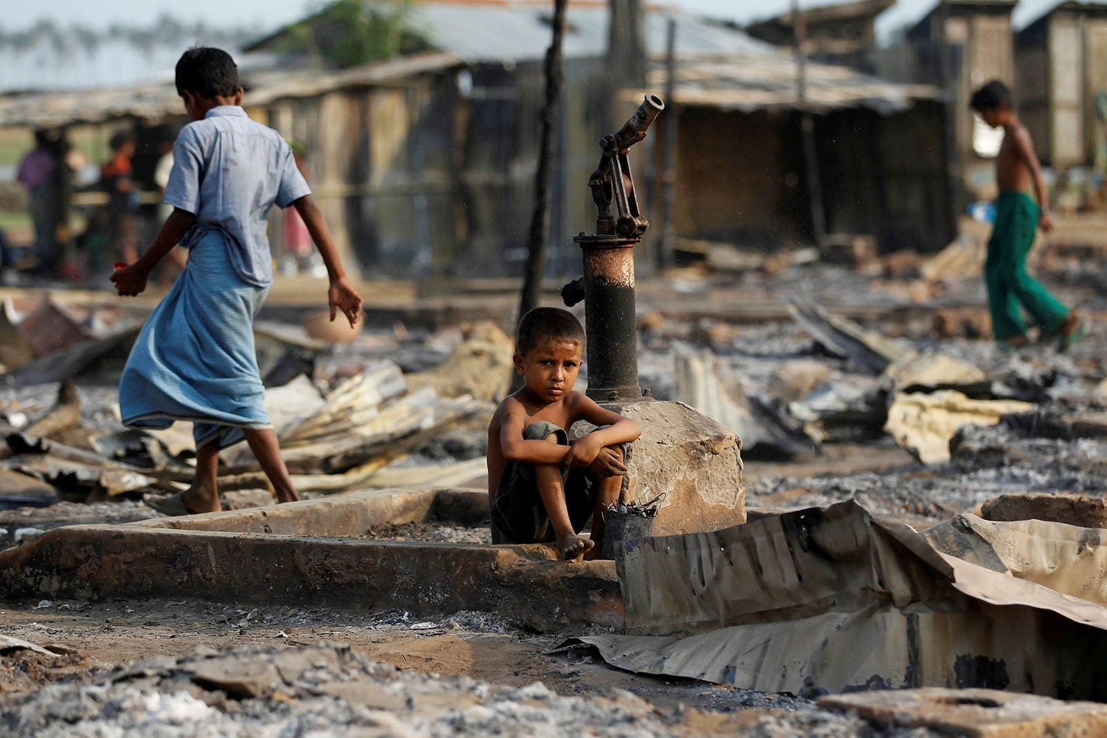 A boy sit in a burnt area after fire destroyed shelters at a camp for internally displaced Rohingya Muslims in the western Rakhine State near Sittwe, Myanmar May 3, 2016.