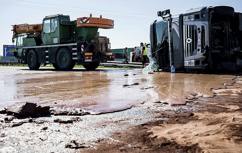 Tons of liquid milk chocolate are spilled and block six lanes on a highway after a truck transporting it overturned near Slupca, in western Poland, on Wednesday, May 9 (AP Photo)