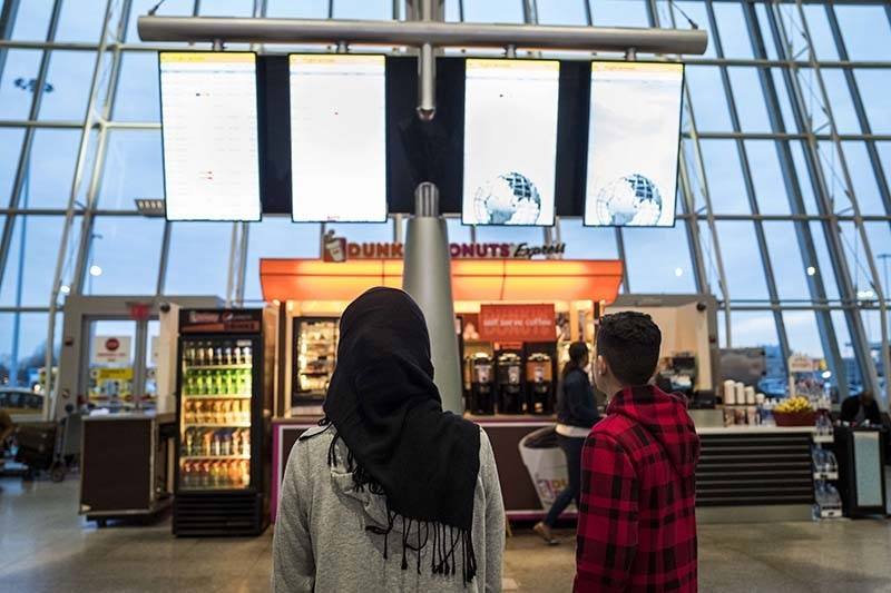 A  young woman wearing a Hijab watches the arrivals board at the international terminal at John F. Kennedy International Airport, March 6, 2017 (AFP Photo)