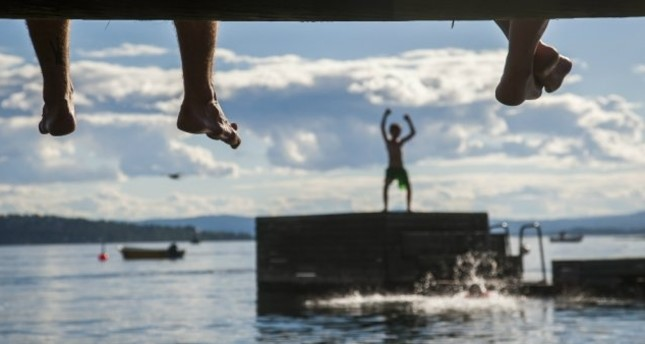 Sitting on the boardwalk parents watch children play and swim from a floating dock off the island of Lindoya in the Oslo fjord on July 18, 2014. (AFP Photo)