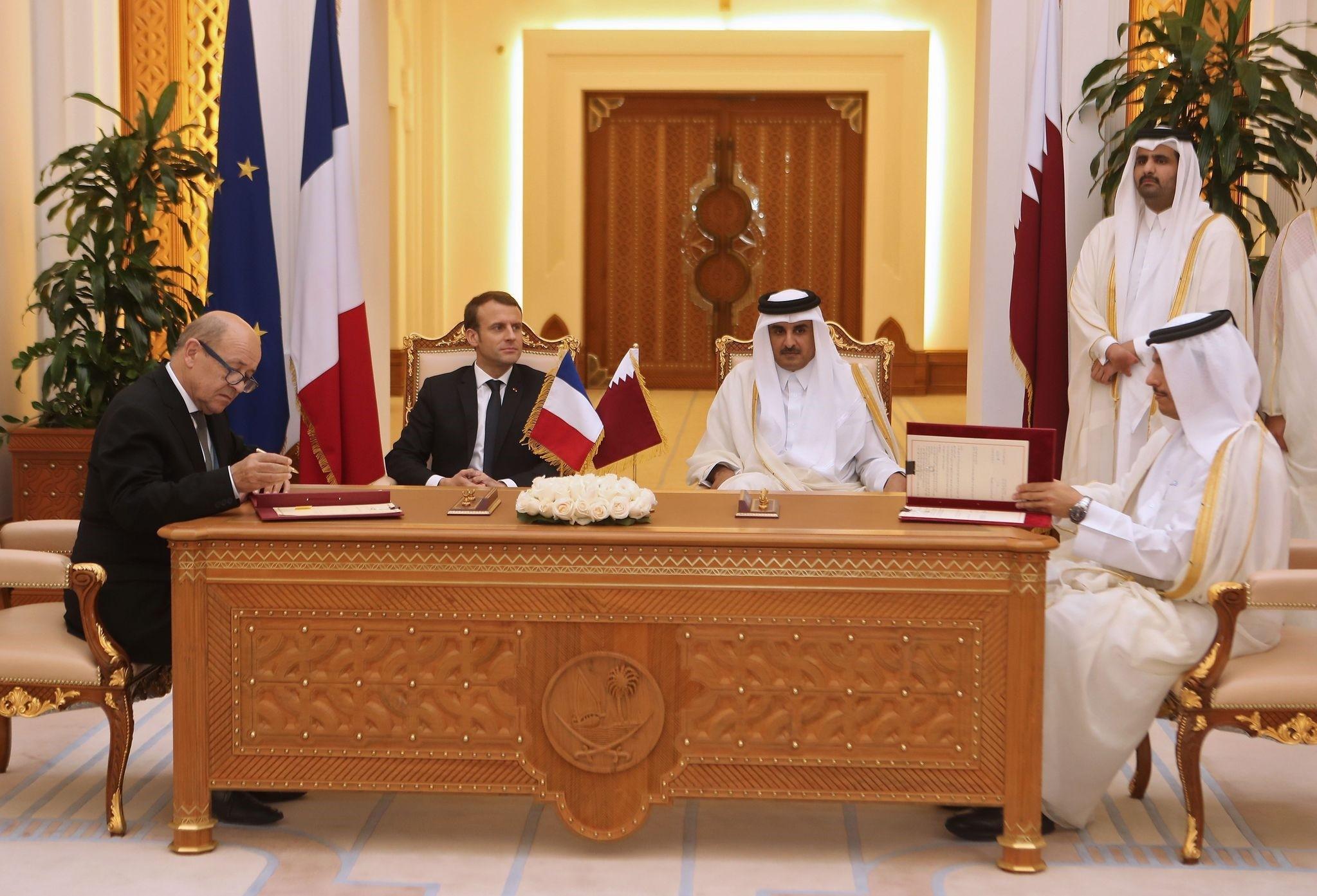 Macron (C-L), Qatari Emir Sheikh Tamim bin Hamad al-Thani (C-R) watch French Foreign Minister Jean-Yves Le Drian and his Qatari counterpart Mohammed bin Abdulrahman al-Thani (R) sign bilateral agreements in Doha on December 7, 2017. (AFP Photo)