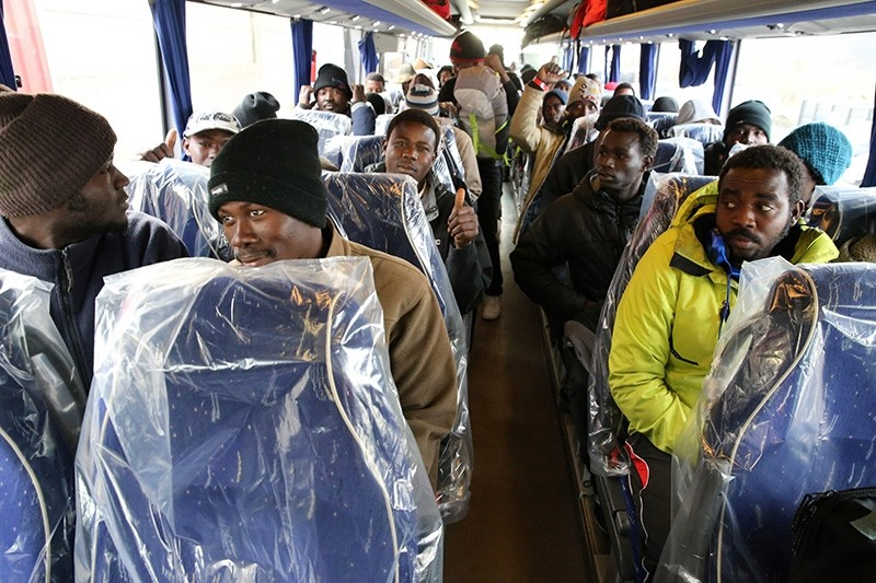 Migrants sit on a bus with plastic covered seats before leaving to reception centres across France, at the ,Jungle, migrant camp in Calais, northern France, on October 26, 2016, during the full evacuation of the camp. (AFP Photo)