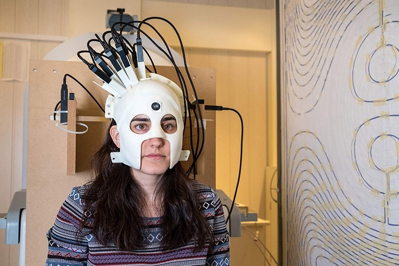 A handout photo released on March 21, 2018 via Nature from Wellcome shows a woman with a brain scanner. (AFP Photo)
