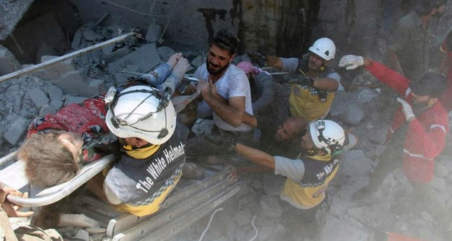This photo shows Syrian White Helmet civil defense workers carry an injured girl on a stretcher after an airstrike hit the northern town of Ariha, in Idlib province, Syria, Saturday, July 27, 2019. (AP Photo)
