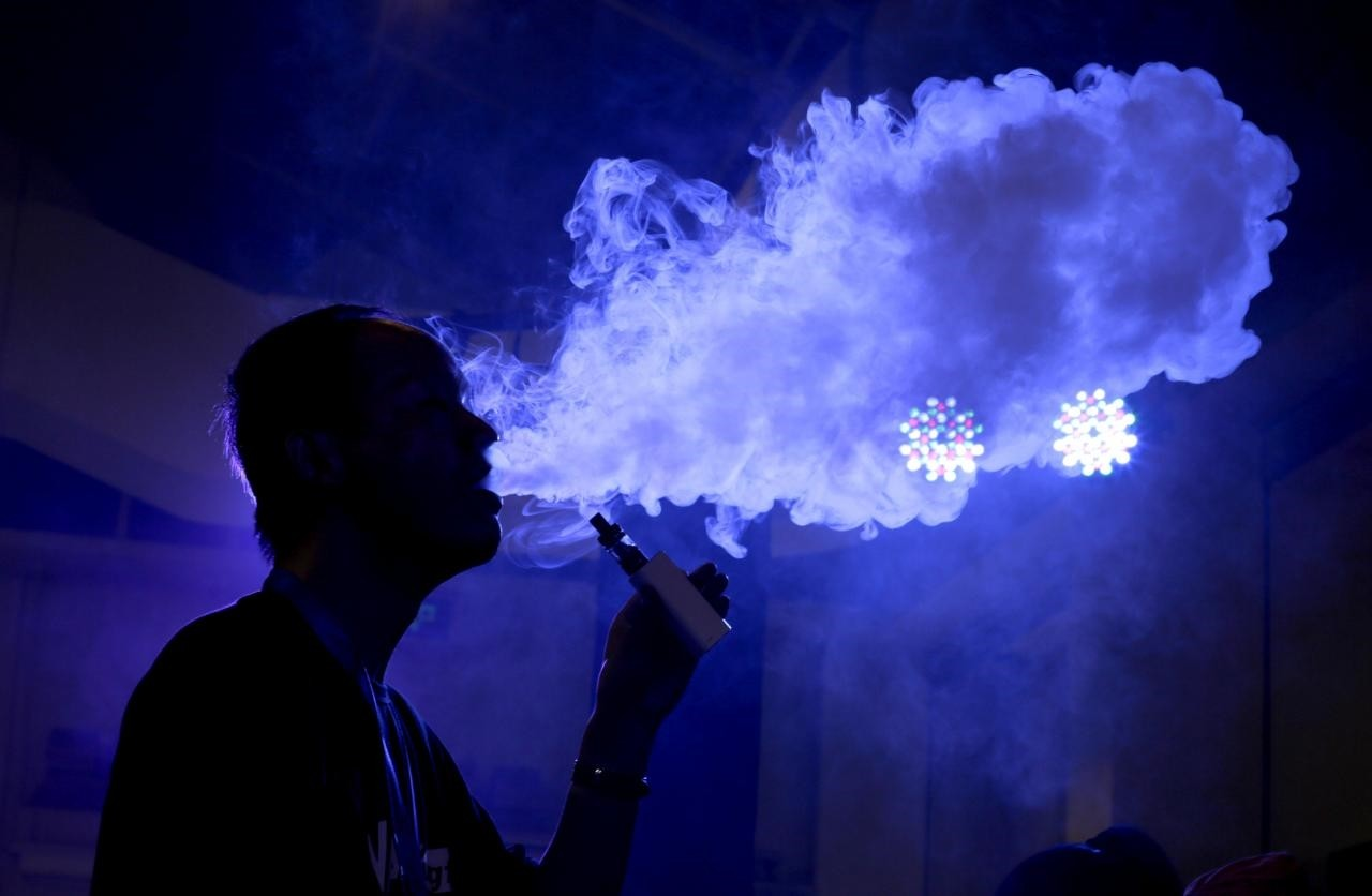 An exhibitor staff member uses an electronic cigarette at Beijing International Vapor Distribution Alliance Expo (VAPE CHINA EXPO) in Beijing, July 24, 2015. (Reuters Photo)