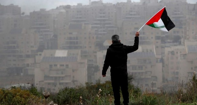 A demonstrator holds a Palestinian flag in the village of Bilin in the Israeli-occupied West Bank, Feb. 7, 2020. REUTERS Photo