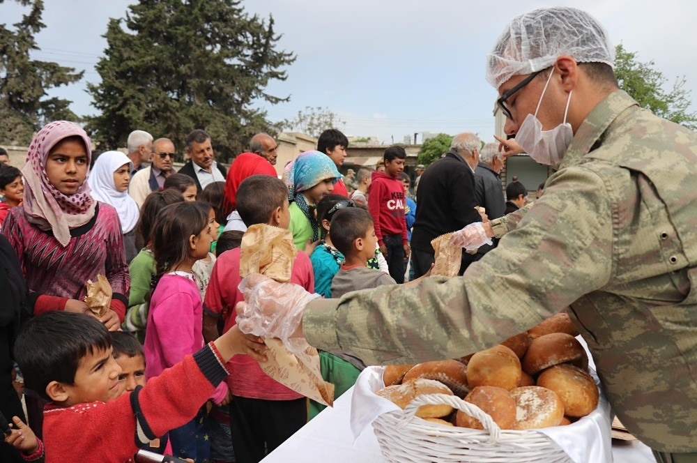 Turkish soldiers distribute bread to locals in Jinderes in Afrin from a mobile oven with the capacity to produce 6,000 loaves of bread a day, April 9.